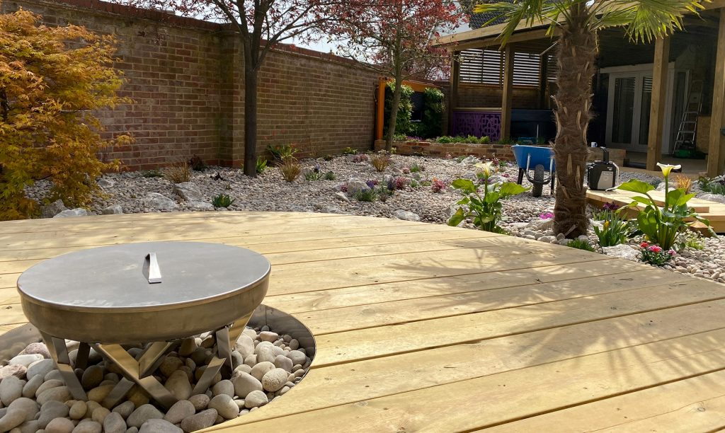 Bio Ethanol fire pit surrounded by wooden decking.