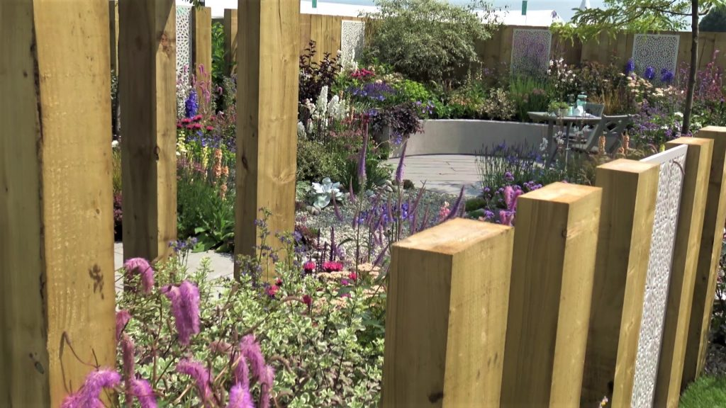 Garden with a view, wooden pergola with all the colourful planting on view. It features a circular paved area with seats.