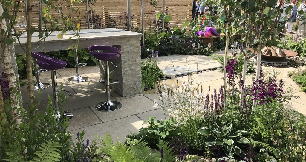 Woodland Fall garden that features a seating area and firepit