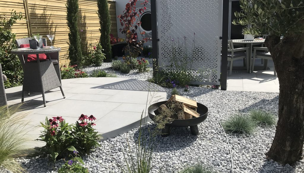 Garden inspired by James Bond features grey wicker chairs and table and a firepit.